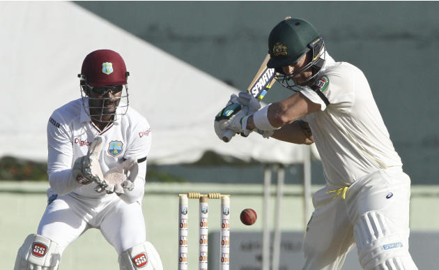Australia's captain Michael Clarke, righ, plays a shot off West Indies' Jason Holder, as wicketkeeper and captain Denesh Ramdin looks on during the opening day of their first cricket Test matc