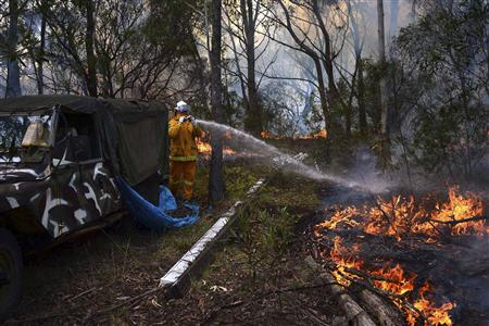 A Rural Fire Service firefighter sprays water onto a small fire burning near a home in western Sydney October 20, 2013. REUTERS/Stringer