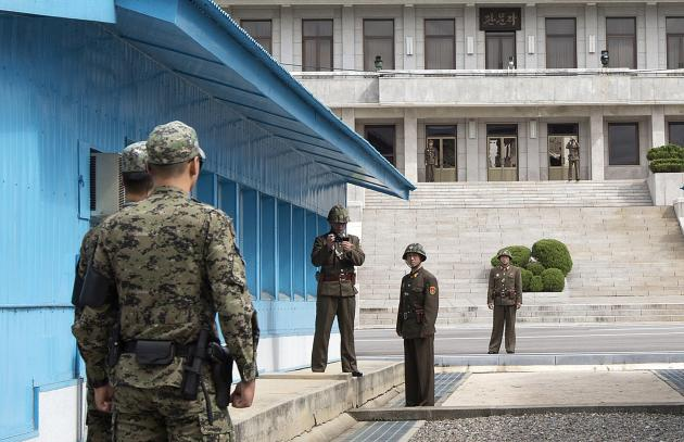 North Korean soldiers stand on the North Korean side, with one using a camera, as South Korean soldiers face them at the U.N. truce village building that sits on the border of the Demilitarized Zone (DMZ), the military border separating the two Koreas, during the visit of U.S. Secretary of Defense Chuck Hagel, in Panmunjom, South Korea September 30, 2013. Hagel toured the Korean DMZ on Monday, at times under the watchful eye of North Korean soldiers, and said the Pentagon had no plan to reduce its 28,500-member force in the South despite budget constraints. REUTERS/Jacquelyn Martin/Pool (SOUTH KOREA - Tags: POLITICS MILITARY)
