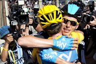 Tour de France runner-up Chris Froome (right) congratulates winner Bradley Wiggins in Paris on Sunday. Froome and Belgium's Jurgen Van den Broeck, fourth in the Tour de France, are to ride in the forthcoming Tour of Spain