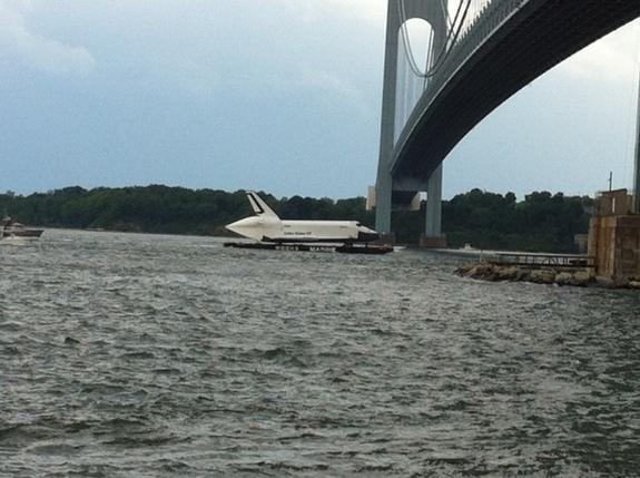 A barge carrying NASA's space shuttle Enterprise prototype passes beneath a bridge in the New York Harbor during a trip from John F. Kennedy airport to a New Jersey port during delivery on June 3, 2012. Enterprise is being delivered to the Intr