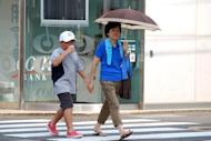 A boy and a woman walk across a street at Shimanto in Kochi prefecture, on Japan's southern island of Shikoku, where Japan's record temperature of 41 degree Celsius (106F) was registered on August 12, 2013. The west of Japan had its hottest ever summer this year, official figures showed Monday after a season in which heatstroke reportedly killed hundreds