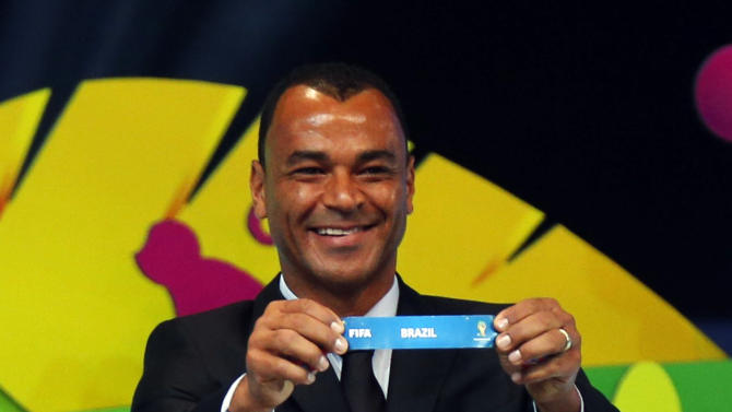 "Former Brazil soccer player Cafu holds the slip showing ""Brazil"" during the draw for the 2014 World Cup at the Costa do Sauipe resort in Sao Joao da Mata"