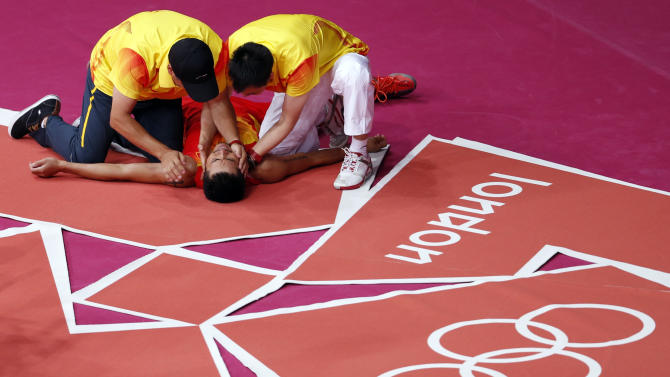 China's Lin Dan lies on the ground as he is congratulated by his coaches after winning his men's singles badminton gold medal match against Malaysia's Lee Chong Wei at the London 2012 Olympic Games at the Wembley Arena
