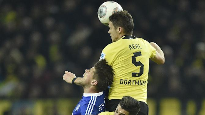 Dortmund's Sebastian Kehl, Schalke's Klaas-Jan Huntelaar of the Netherlands and Dortmund's Nuri Sahin of Turkey, from up, challenge for the ball during  the German Bundesliga soccer match between Borussia Dortmund and FC Schalke 04 in Dortmund,  Germany, Tuesday, March 25, 2014