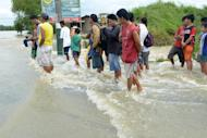 Stranded commuters stand in flood water on a road in northern Philippines on October 12, 2013