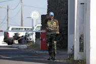 An Indian UN peacekeeper stands guard at the gates of the UN headquarters, in the demilitarized United Nations Disengagement Observer Force (UNDOF) zone, near Qunetra in the Golan Heights on May 7, 2013