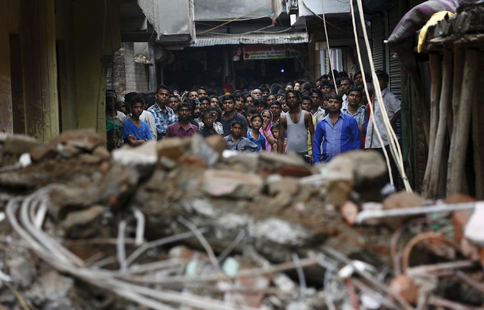 Onlookers stand at the site of a collapsed building in New Delhi