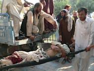 Afghan men carry a wounded man as he arrives at a hospital in Jalalabad. A suicide bomber targeted an Afghan government official at a village funeral near the Pakistan border on Tuesday, killing at least 20 people and wounding dozens more in one of the deadliest attacks of the year