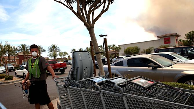 Jason Moore, 17, wears a mask protect to himself from the smoke produced by the Carpenter 1 fire, seen in background at right, while working in northwest Las Vegas Tuesday, July 9, 2013. The wildfire, which has grown to 19,000 acres, began July 1. (AP Photo/Las Vegas Review-Journal, Jessica Ebelhar)