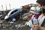 People covering their faces pass a car in debris after super typhoon Haiyan battered Tacloban City, in central Philippines November 13, 2013. REUTERS/Edgar Su