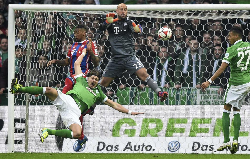 Bayern Munich's goalkeeper Pepe Reina and Jerome Boateng jump for the ball with Werder Bremen's Sebastian Proedl during their German Bundesliga first division soccer match in Bremen