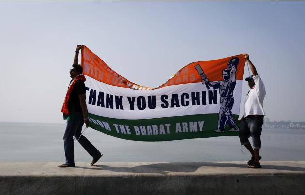 Cricket fans walk on a sea wall while holding a banner in tribute to Indian cricketer Sachin Tendulkar outside a stadium in Mumbai