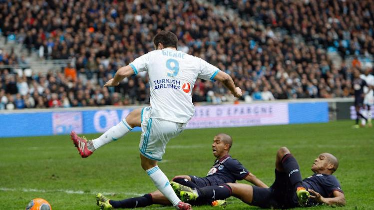 Marseille's French forward Andre-Pierre Gignac, left, challenges for the ball with Bordeaux's Brazilian defender Carlos Henrique dos Santos Souza, right, and Bordeaux's Brazilian defender Ferreira Filho Mariano, during their League One soccer match, at the Velodrome Stadium, in Marseille, southern France, Sunday, Dec. 22, 2013