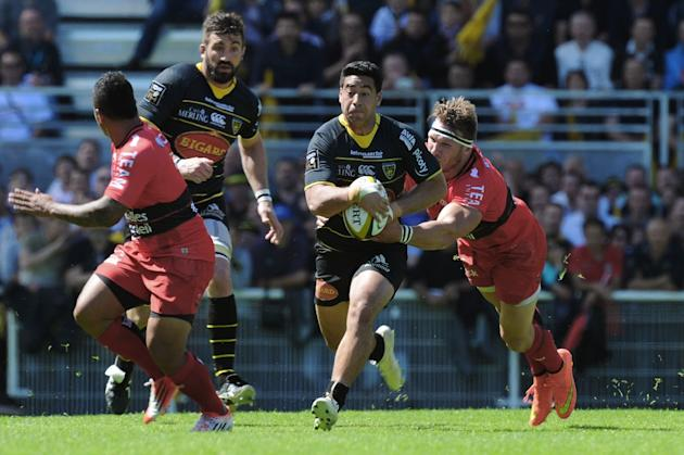 La Rochelle's Australian centre Malietoa Hingano (centre) is tackled during the French Top 14 rugby union match against Toulon at the Marcel Deflandre stadium in La Rochelle, western France on Apr