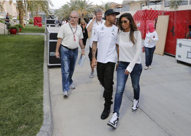 Mercedes Formula One driver Hamilton of Britain walks with his girlfriend Scherzinger towards the team building after the second in-season test at Bahrain International Circuit (BIC) in Sakhir south o