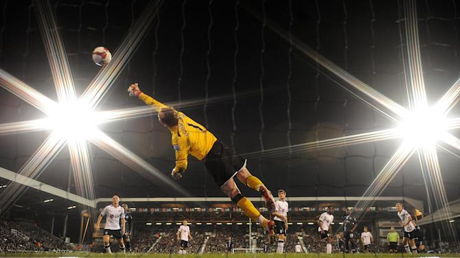 Fulham's Mark Schwarzer dives full length under the floodlights at Craven Cottage  - Graham Chadwick (Daily Mail)
