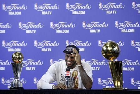 Heat's James sits with the Larry O'Brien Trophy and the Bill Russell MVP Trophy after his team defeated the Spurs in Game 7 to win the NBA Finals basketball playoff in Miami