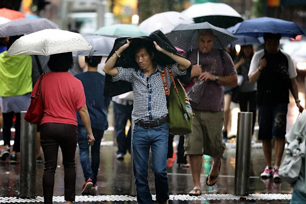 SINGAPORE - FEBRUARY 14: Shoppers brave the rain along Orchard Road on February 14, 2013 in Singapore. The government white paper revealed Singapore's population may increase 30% to over 6.9 million by 2030, with nearly half the population expected to be foreign-born. Many local residents are critising the plan, concerned about the added strain on housing, transportation and healthcare and the diminishing identity of the Singaporean community. (Photo by Suhaimi Abdullah/Getty Images)