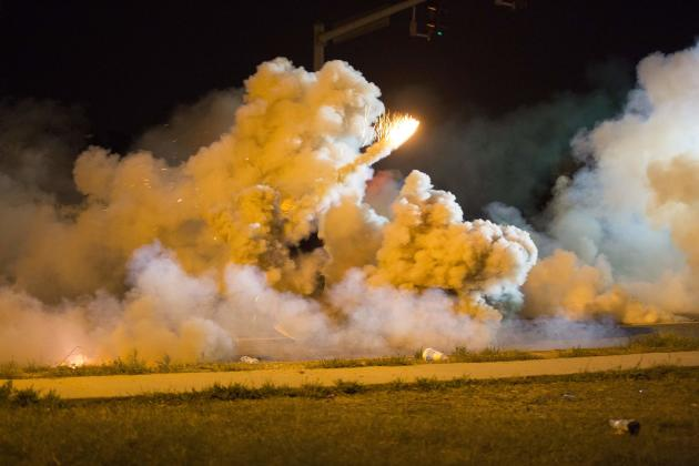 A protester throws back a smoke bomb while clashing with police in Ferguson, Missouri August 13, 2014. Police in Ferguson fired several rounds of tear gas to disperse protesters late on Wednesday, on the fourth night of demonstrations over the fatal shooting last weekend of an unarmed black teenager Michael Brown, 18, by a police officer on Saturday after what police said was a struggle with a gun in a police car. A witness in the case told local media that Brown had raised his arms to police to show that he was unarmed before being killed. Picture taken August 13, 2014. REUTERS/Mario Anzuoni (UNITED STATES - Tags: CRIME LAW)