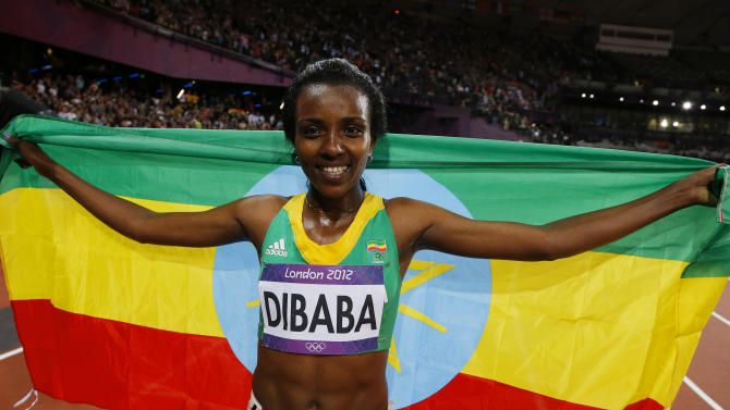 Ethiopia's Tirunesh Dibaba celebrates with her national flag after she won the women's 10,000m final at the London 2012 Olympic Games at the Olympic Stadium