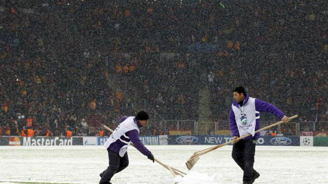 Workers rush to clean the snow from the pitch in Istanbul.