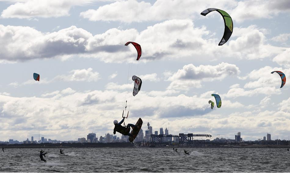 Kite surfers take advantage of strong westerly winds and choppy waves on Sydney's Botany Bay