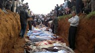 "A picture released by the Local Coordination Committees in Syria (LCC) shows people standing around a mass grave in the town of Taftnaz, on April 5, 2012. UN investigators say they have ""reasonable grounds"" to believe both sides in Syria have used chemical weapons, and warned that crimes against humanity were now occurring daily in the war-torn country"