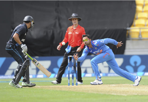 India's Virat Kohli, right, fields off his own bowling in front of New Zealand's Ross Taylor in the fifth and final one-day international cricket match in Wellington, New Zealand, Friday, Jan. 31,
