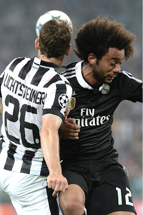 Juventus' Stephan Lichtsteiner jumps for the ball with Real Madrid Marcelo during the Champions League, semifinal soccer match between Juventus and Real Madrid at the Juventus Stadium in Turin, It