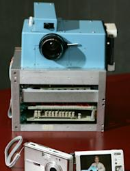 FILE - In this Aug. 17, 2005 file photo, Kodak's prototype digital camera built in 1975 by Eastman Kodak engineer Steven J. Sasson, is shown next to Kodak's latest digital camera, the EasyShare One, at Kodak headquarters in Rochester, N.Y. Buffeted by fierce foreign competition, then blindsided by a digital revolution, photography icon Eastman Kodak Co. is teetering on a financial precipice after a quarter-century of failed efforts to find its focus. (AP Photo/David Duprey, File)