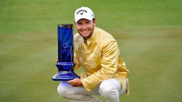 : This handout photo taken and received on April 22, 2012 shows Branden Grace of South Africa posing with the trophy following his victory at the Volvo China Open