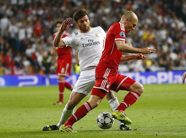 Real's Xabi Alonso stops Bayern's Arjen Robben, right, during a  Champions League semifinal first leg soccer match between Real Madrid and Bayern Munich at the Santiago Bernabeu stadium in Mad