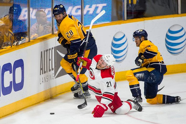 NASHVILLE, TN - OCTOBER 8: James Wisniewski #21 of the Carolina Hurricanes hits the ice as Paul Gaustad #28 and Viktor Arvidsson #38 of the Nashville Predators go after the puck during a NHL game at Bridgestone Arena on October 8, 2015 in Nashville, Tennessee. (Photo by Ronald C. Modra/NHL/Getty Images)