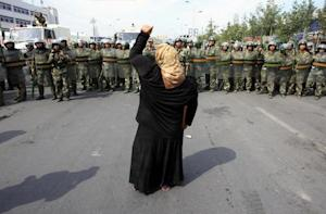 Woman on crutch shouts at Chinese paramilitary police wearing riot gear as crowd of angry locals confront security forces on street in Urumqi