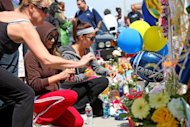 Wellwishers pay their respects at a memorial outside of Junior Seau's beach home in Oceanside, California. Former NFL star Seau committed suicide by shooting himself in the chest, autopsy results confirmed on Thursday, according to San Diego County authorities