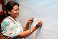 Shanta Chaudhary, rights campaigner and former 'kamlari' girl, adds the first signature to a banner urging for the elimination of child labour from Nepal, at a media conference in the capital Kathmandu. Chaudhary was eight years old when her parents sold her into effective slavery at the house of a stranger in southwestern Nepal