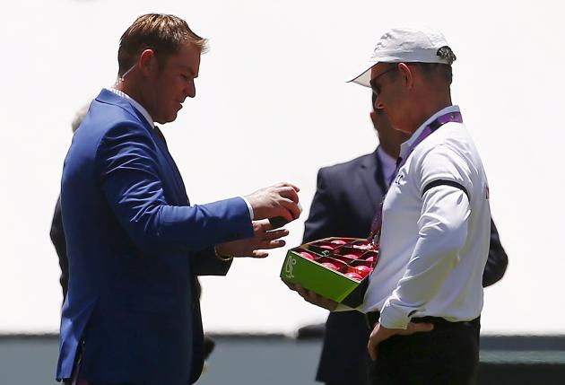 Former Australian bowler Warne holds a pink cricket ball next to an official holding a box containing them before the start of the first day of the third cricket test match between Australia and New Z