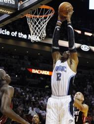 Orlando Magic's Dwight Howard (12) shoots as Miami Heat's Joel Anthony (50), Shane Battier (31) and Mario Chalmers (15) watch during the first half of an NBA basketball game, Sunday, March 18, 2012, in Miami. (AP Photo/Lynne Sladky)