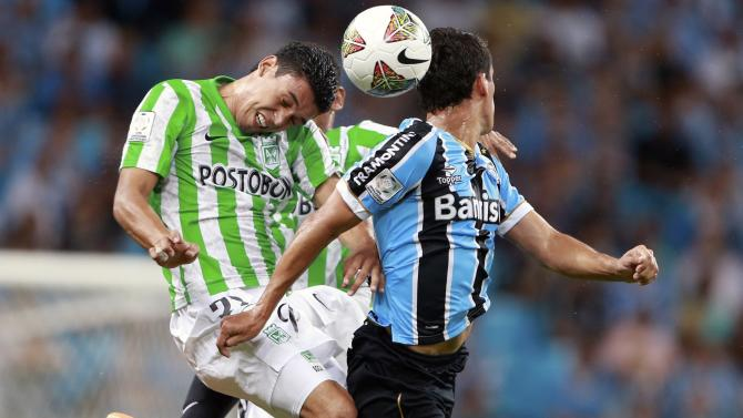Bocanera of Colombia's Atletico Nacional jumps for the ball Riveros of Brazil's Gremio during their Copa Libertadores match in Porto Alegre