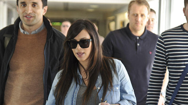 Pregnant Kim Kardashian went for a casual look for a flight back to LA from Heathrow. Copyright [Splash]