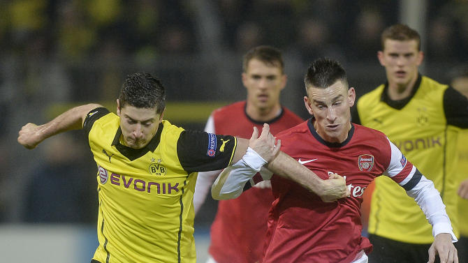 Dortmund's Robert Lewandowski, left, and Arsenal's Laurent Koscielny challenge for the ball during the Champions League group F soccer match between Borussia Dortmund and Arsenal FC in Dortmund, Germany, Wednesday, Nov. 6, 2013