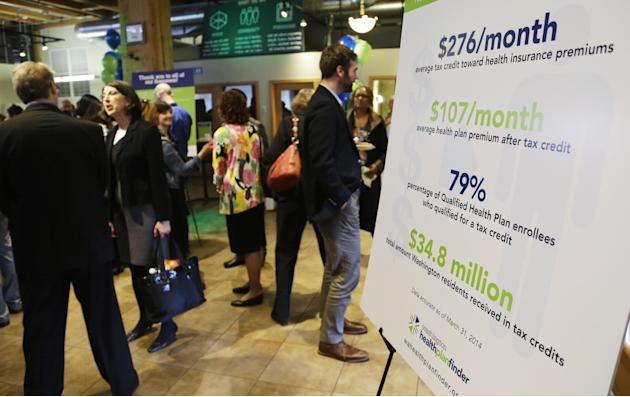 A chart showing the average premium cost and tax credit data for people who enrolled in the Washington state healthcare exchange is shown at an event Wednesday, April 23, 2014 in Seattle to highlight