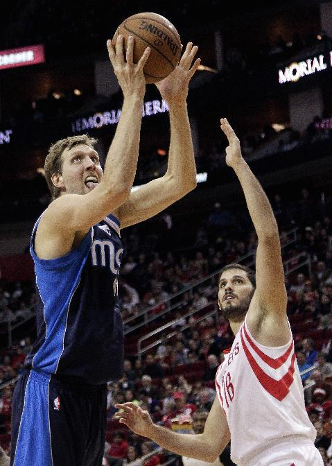 Dallas Mavericks forward Dirk Nowitzki (41), of Germany, drives past Houston Rockets' Omri Casspi (18) for a layup during the first half of an NBA basketball game, Monday, Dec. 23, 2013, in Houston