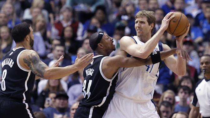 Dallas Mavericks forward Dirk Nowitzki (41) of Germany looks to pass against  Brooklyn Nets defenders Paul Pierce (34)  and Deron Williams (8) during the first half of an NBA basketball game Sunday, March 23, 2014, in Dallas