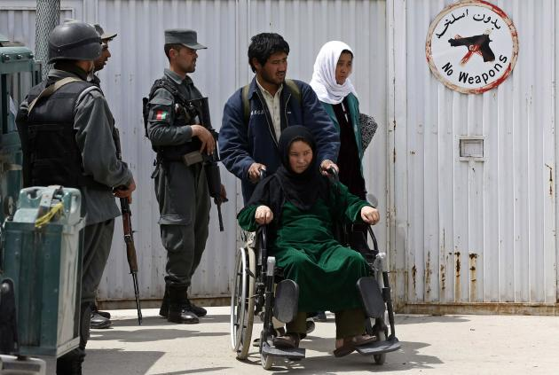 A patient, on a wheelchair, is helped by her relatives while policemen stand guard at the gate of Cure Hospital after three Americans were killed in Kabul