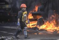 A boy walks by a truck on fire during clashes between anti-government protesters and Interior Ministry members in Kiev February 18, 2014. REUTERS/Andrew Kravchenko/Pool