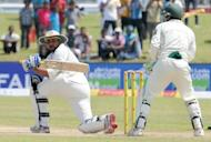 Sri Lankan batsman Tillakaratne Dilshan (left) plays a shot as Pakistan wicketkeeper Adnan Akmal looks on during their Test Match in Galle. Sri Lanka set Pakistan a tough target of 510 to win the first Test in Galle after the hosts declared their second innings at 137-5 after tea on the third day