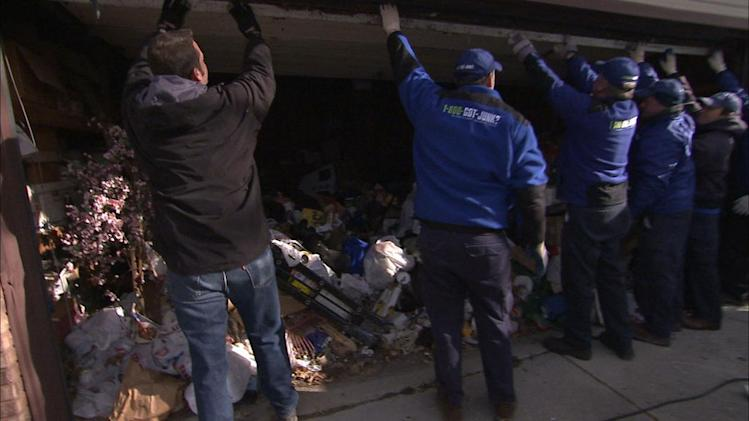 "Cory and a line of 8 guys lifting up the garage door in season premiere of ""Hoarders."""