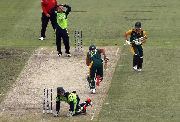 Ireland's Andy McBrine reacts as wicketkeeper Gary Wilson rests on his knees while South Africa's David Miller and Rilee Rossouw run between wickets during their Cricket World Cup match in Can